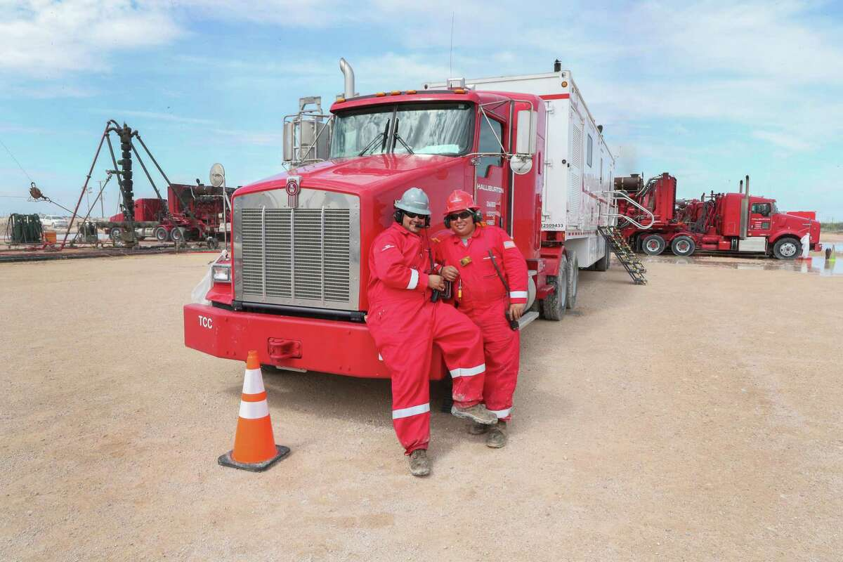 Halliburton employees pose for a photo at a three wellhead fracking site Monday, June 26, 2017, in Midland.