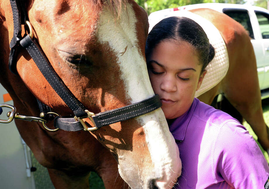 Hailey Hayes hugs, on Friday, Pistol a 10-year-old mixed breed who was stolen earlier this week and later reclaimed. Pistol who is trained as a therapy horse was recovered in Louisiana and has returned to helping Hayes combat the effects of Devic's disease which effects her optical and spinal nerves.      Photo taken Friday, July 07, 2017 Guiseppe Barranco/The Enterprise Photo: Guiseppe Barranco, Photo Editor