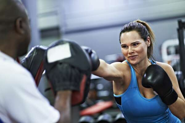 Healthy female wearing boxing gloves, sparring with black male personal trainer in leisure centre.