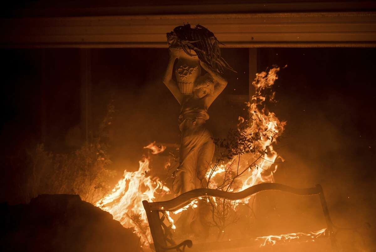 CALIFORNIA WILDFIRES: JULY 2017 Flames from a wildfire surround a lawn statue near Oroville, Calif., on Sunday, July 9, 2017. Evening winds drove the fire through several neighborhoods leveling homes in its path.
