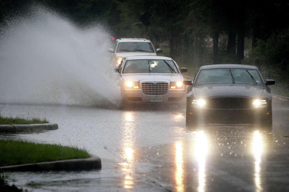 Cars navigate around and through high waters on Research Forest Drive near Crownridge Drive after heavy rain Monday, July 10, 2017, in The Woodlands. Photo: Michael Minasi/Houston Chronicle