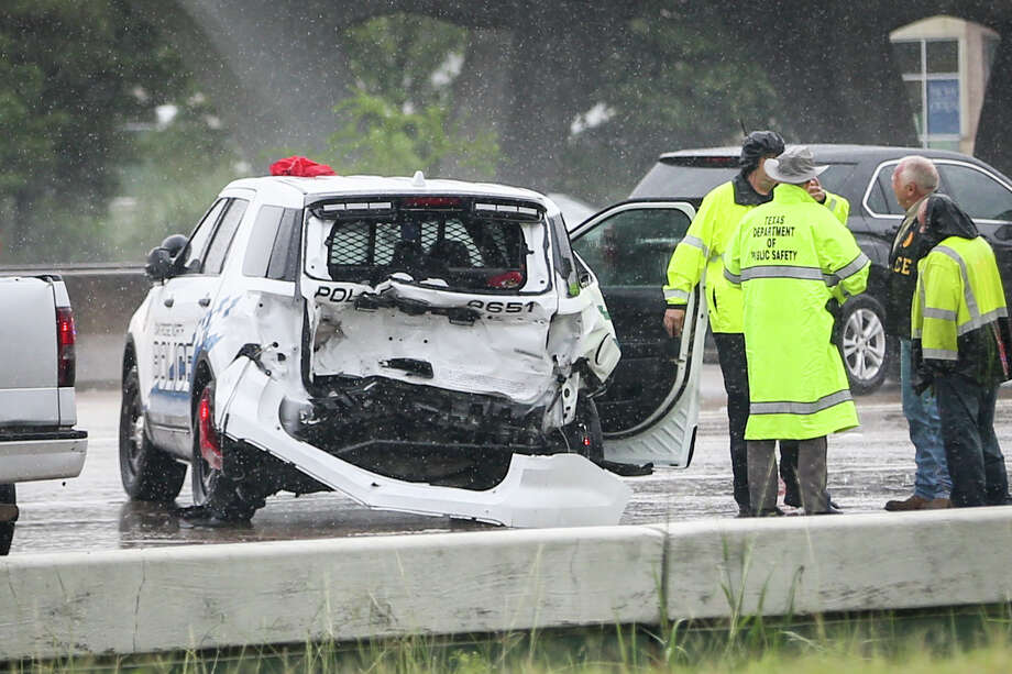 Emergency responders secure the scene of a traffic stop collision involving 3 vehicles, including an Oak Ridge North Police vehicle, on Monday, July 10, 2017, on the southbound exit ramp of Interstate-45 North near Timberloch Place in The Woodlands. Photo: Michael Minasi/Houston Chronicle