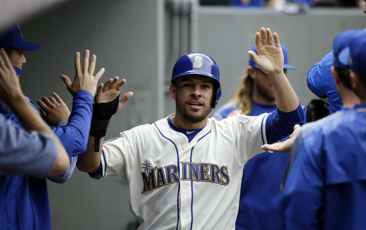 Seattle Mariners' Danny Valencia is congratulated after scoring against the Oakland Athletics in a baseball game Sunday, July 9, 2017, in Seattle. (AP Photo/Elaine Thompson)