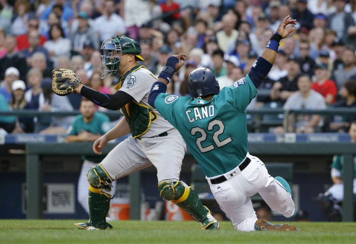 Seattle Mariners' Robinson Cano (22) slides home to score as Oakland Athletics catcher Ryan Lavarnway waits for the throw during the third inning of a baseball game, Friday, July 7, 2017, in Seattle. (AP Photo/Ted S. Warren)