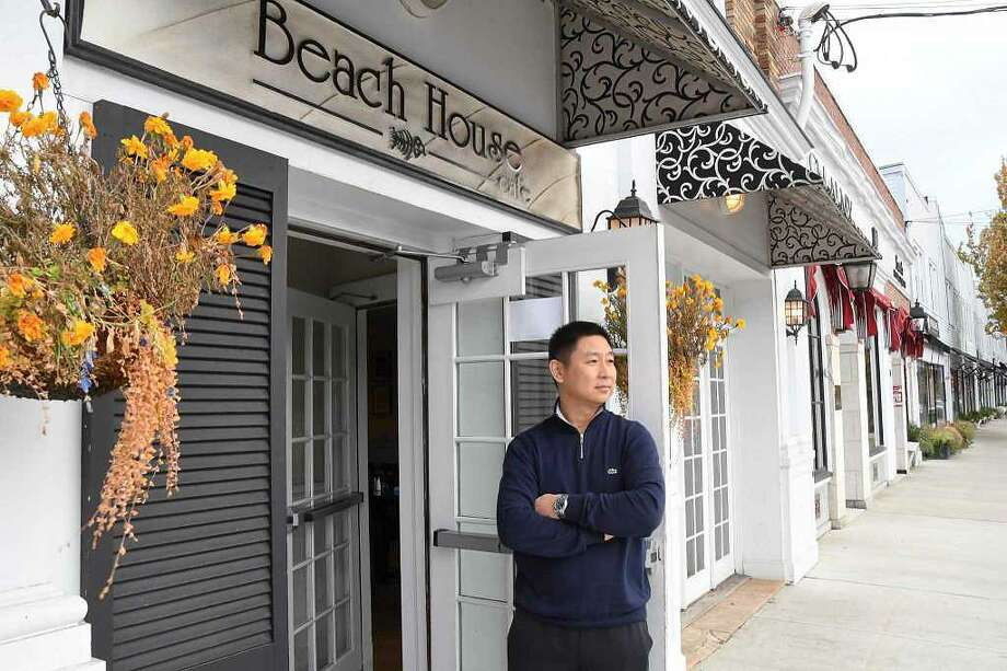 At the Beach House Cafe, chef and co-owner Kane Xu stands outside his restaurant on Sound Beach Avenue in Greenwich, Conn. Photo: Bradley E. Clift / Hearst Connecticut Media / Stamford Advocate