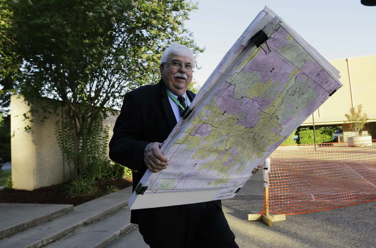 Russ Tidwell, a former lobbyist who is helping minority rights groups sue Texas over Republican-drawn voting maps holds a set of maps as he makes his way to the federal courthouse on July 10, 2017, in San Antonio.