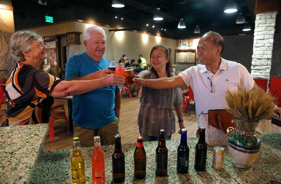 June Milner (left), her husband Jerry Hagerty, Hongkham Thepkaysone and her husband Bounchanh Thepkaysone toast in the Budweiser tasting room. Photo: Paul Chinn, The Chronicle
