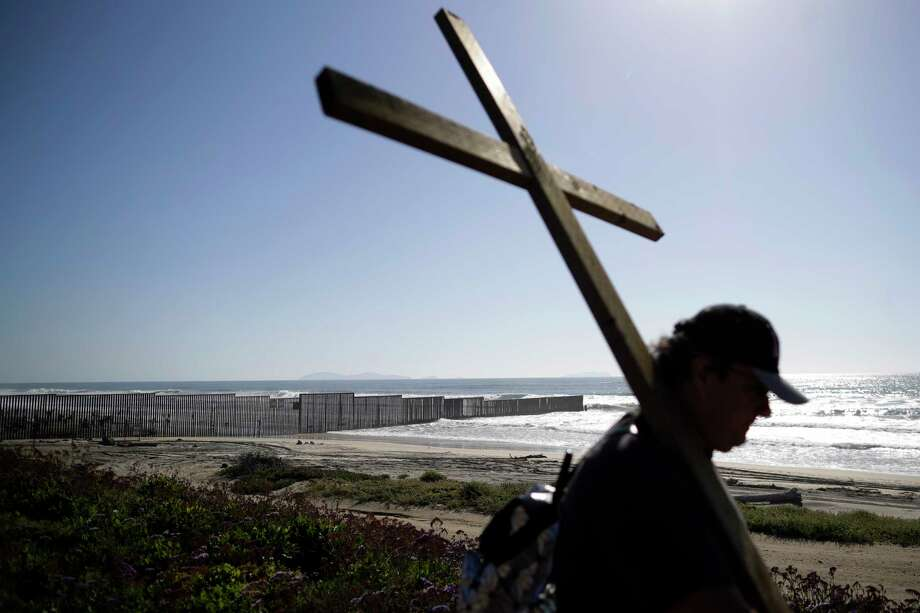 ***TO GO WITH WORLD WALLS PROJECT** In this April 3, 2017, picture, Winston Pinuela carries a cross near the where the border structure separating Tijuana, Mexico, and San Diego meets the Pacific Ocean in San Diego. (AP Photo/Gregory Bull) Photo: Gregory Bull, Associated Press / Copyright 2017 The Associated Press. All rights reserved.