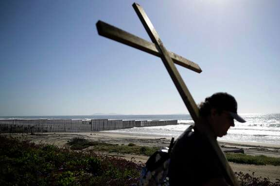 ***TO GO WITH WORLD WALLS PROJECT** In this April 3, 2017, picture, Winston Pinuela carries a cross near the where the border structure separating Tijuana, Mexico, and San Diego meets the Pacific Ocean in San Diego. (AP Photo/Gregory Bull)