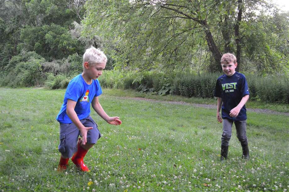 Baxter Bradfield, 7, left, and Ollie Forrest, 7, both of New Canaan, try to catch a flying critter at the Night of 1,000 Fireflies woodland walk at New Canaan Nature Center, Saturday, July 8, 2017, in New Canaan, Conn. Photo: Jarret Liotta / For Hearst Connecticut Media / New Canaan News Freelance