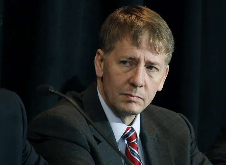 """FILE - In this Oct. 7, 2015, file photo, Consumer Financial Protection Bureau Director Richard Cordray listens to a speaker during a hearing in Denver. The CFPB has decided to broadly ban the use of so-called arbitration clauses from financial products. Cordray said mandatory arbitration clauses are a way for banks and other financial companies to """"sidestep the legal system."""" Consumer advocates have been pushing for years for stricter federal regulation of these types of clauses. But the move is likely to face pushback from the banking industry and the Republican-controlled Congress. (AP Photo/Brennan Linsley, File)"""