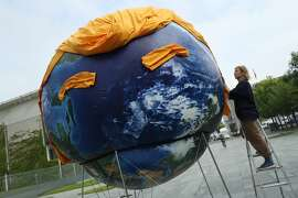 BERLIN, GERMANY - JUNE 29:  An activist prepares a balloon painted to look like planet Earth and decorated with orange hair and eyebrows in the likeness of U.S. President Donald Trump during a climate protest prior to a meeting of European Union leaders at the Chancellery on June 29, 2017 in Berlin, Germany. EU leaders are meeting today ahead of theupcoming G20 summit in Hamburg.  (Photo by Sean Gallup/Getty Images)
