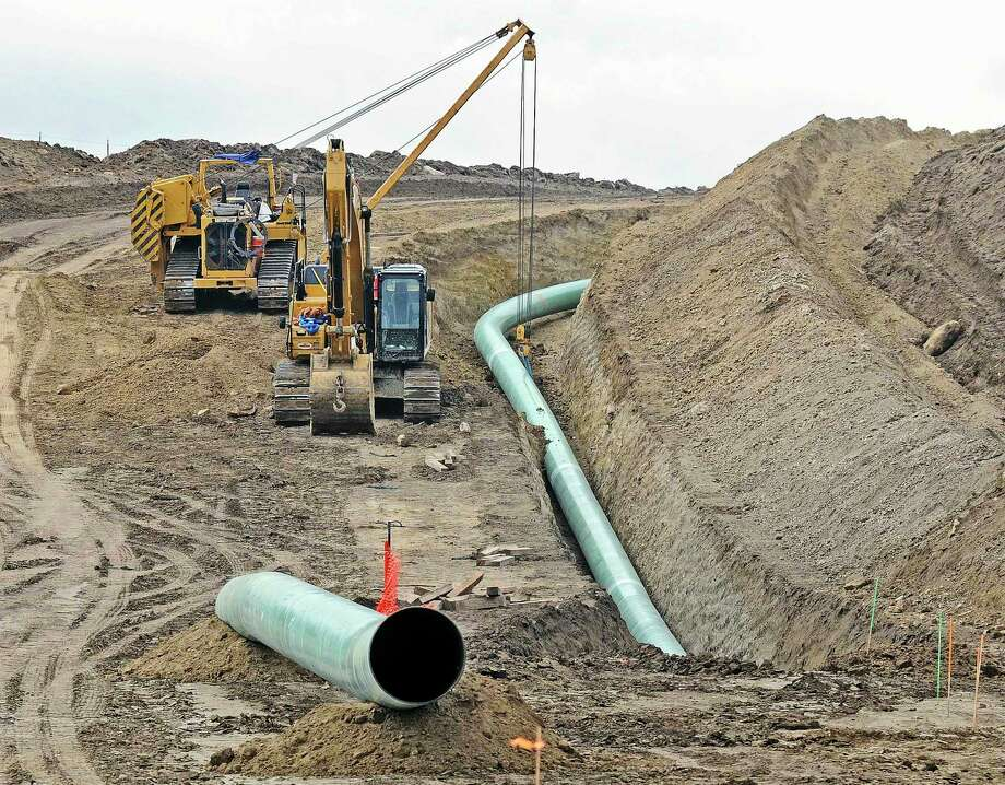 FILE - In this Oct. 5, 2016, file photo, heavy equipment is seen at a site where sections of the Dakota Access pipeline were being buried near the town of St. Anthony in Morton County, N.D. The 1,200-mile line carrying North Dakota oil through South Dakota and Iowa to a distribution point in Illinois began commercial service Thursday, June 1, 2017. (Tom Stromme/The Bismarck Tribune via AP, File) Photo: Tom Stromme, MBO / The Bismarck Tribune
