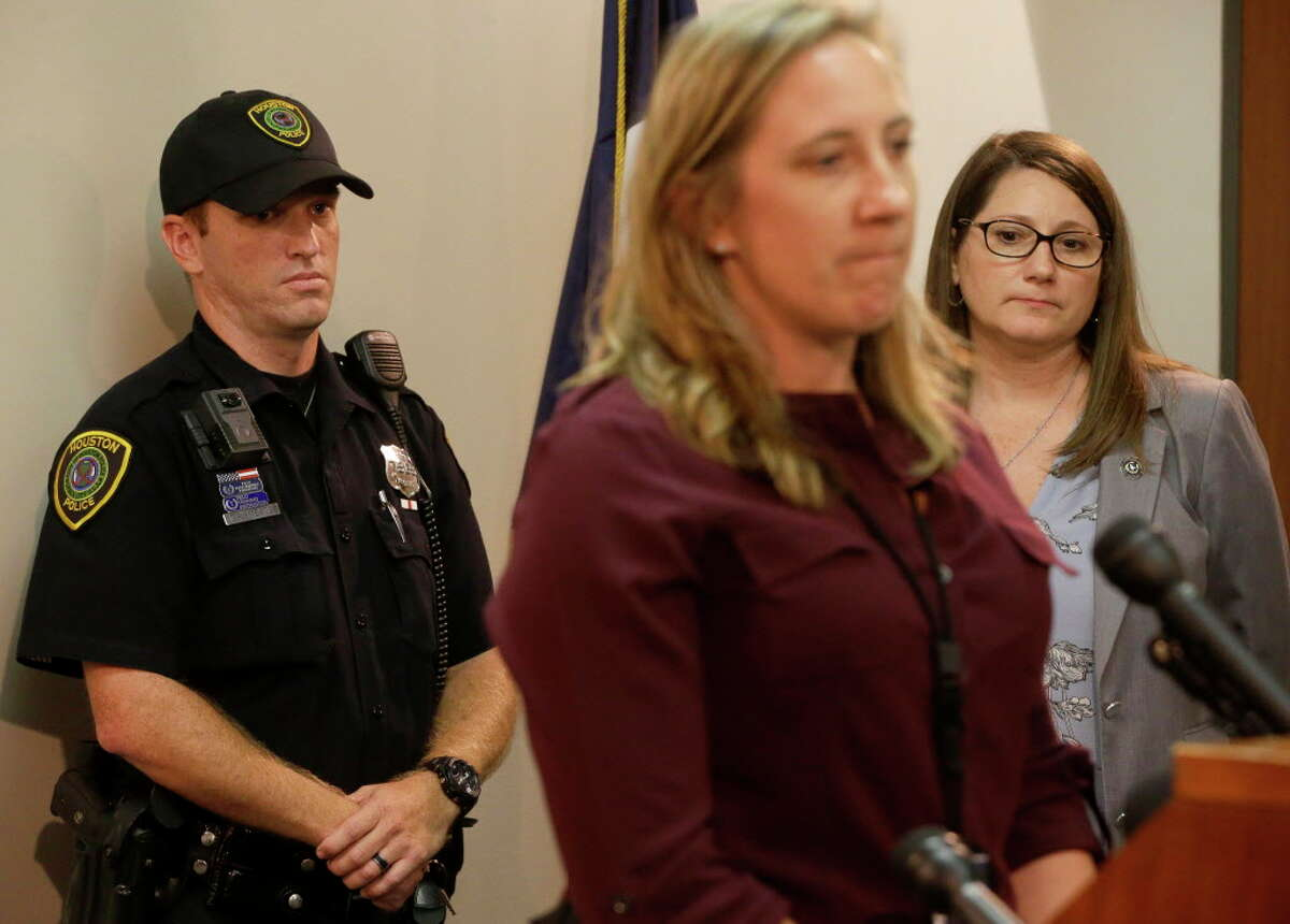 Houston Police Officer Chris Meade, left, listens as HPD Lt. Jessica Anderson, center, speaks along with JoAnne Musick, right, of the Harris County District Attorney, during a media conference at the District Attorney office,1201 Franklin, Monday, July 10, 2017, in Houston. Officer Meade discovered a box truck Sunday afternoon with a dozen persons, including a minor girl, locked inside the cargo bay. All of the persons who were smuggled are believed to be from Latin America. Three people are charged with human smuggling in the case. They are Priscila Perez Beltran, 21, Adela Alvarez, 26, and Nelson Cortes Garcia, 27.