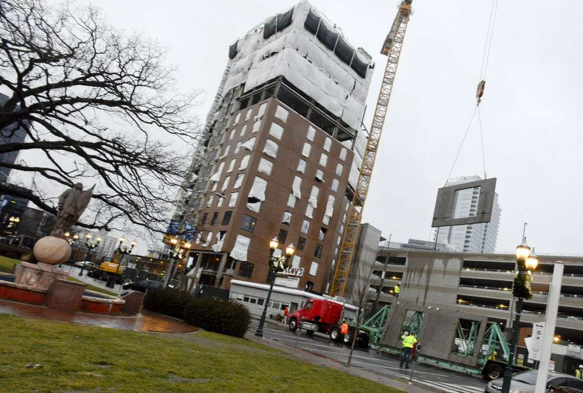 A crane hoist a prefabricated brick facade for the Park Square West IV development in Stamford in January. The construction is expected to be completed in October.