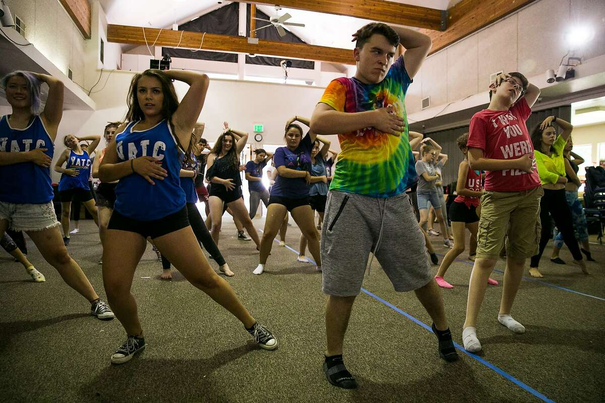 Matthew McCoy, center, and Amanda Domb, right, dance with the Young Actors Camp group at Camp MayMac in Felton, Calif. Sunday, July 9, 2017.