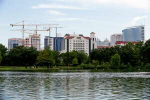 The Texas Medical Center is reflected in McGovern Lake at Hermann Park Monday, July 10, 2017 in Houston.