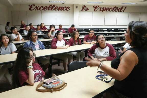 Heights High School Campus Instructional Technologist Tisha Mesa talks to students Monday in Houston. The school and other campus' will benefit from the Raise Your Hand Texas Foundation launching Raising Texas Teachers program.