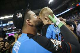 Oakland Athletics first baseman Yonder Alonso (17) kisses his one year old son, Troy, during batting practice for the American League Team before the Home Run Derby at Marlins Park July 10, 2017 in Miami. (Will Vragovic/Tampa Bay Times/TNS)