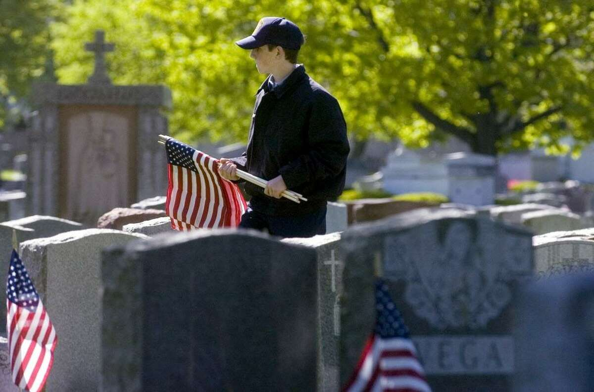 Stamford_051708_ Harrison Martell, of Greenwich and a United States Naval Sea Cadet, helps members of VFW Post 9617 and other volunteers place flags on veterans graves at St. John's Cemetery in preparation for Memorial Day. Kathleen O'Rourke/Staff photo Staff Photo Kathleen O'Rourke