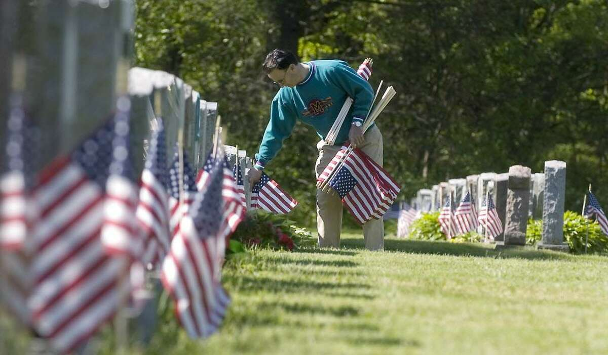 Stamford_051708_ Tony Panaro, of Stamford, helps members of VFW Post 9617 and other volunteers place flags on veterans graves at St. John's Cemetery in preparation for Memorial Day. Kathleen O'Rourke/Staff photo Staff Photo Kathleen O'Rourke