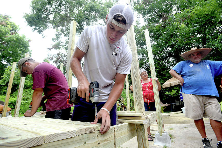 Josef Harris (left) and Riley Durham secure floor boards into place as adult group member Wesley Capps looks on while their crew with this year's UMARMY (United Methodist Action Reach-out Mission) work on building a wheelchair ramp at a home in Beaumont Monday. The annual summer program, which is being hosted locally at Wesley United Methodist Church, brings together 60 youth and adult volunteers from three different regional United Methodist Church for a week. This year, members from Atascocita, Lufkin, and Angleton United Methodist Churches are working in Beaumont, helping to paint houses, do repair work, and build wheelchair ramps for 7 area clients in need of assistance. Photo taken Monday, July, 10, 2017 Kim Brent/The Enterprise Photo: Kim Brent / BEN