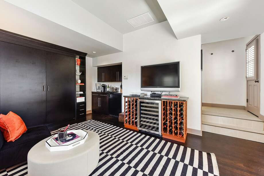 The media room includes a bar area and built-in shelving. Photo: Open Homes Photography