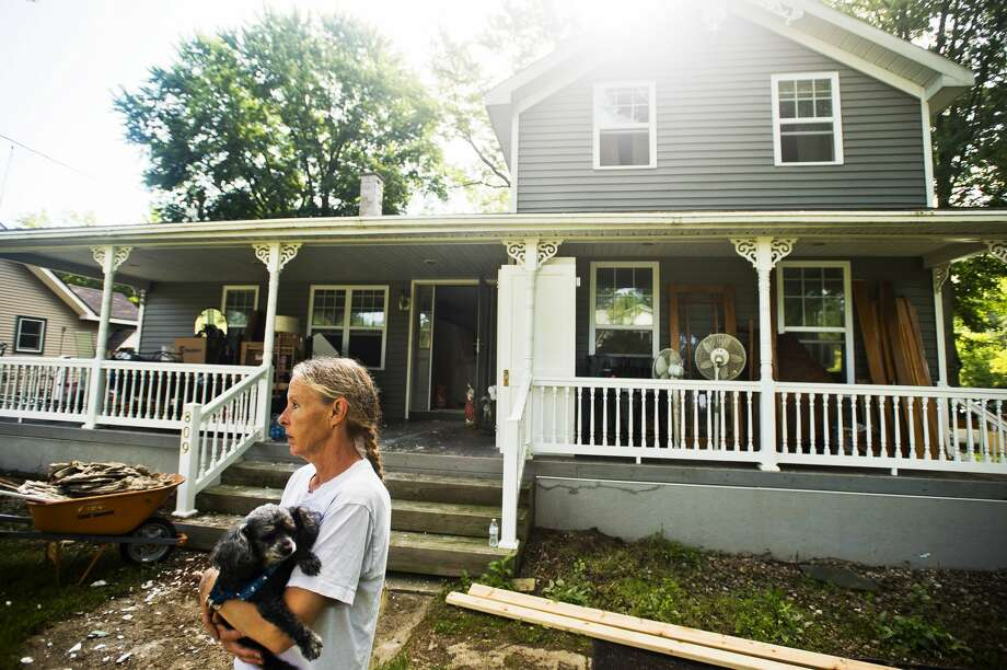 Peggy Sue Ginter stands in her front yard with her dog, Jesse, as a group from Team Rubicon works to gut the inside of her home, which was severely damaged by recent flooding, on Tuesday, July 11, 2017 on Atwell Street near Poseyville Road. Photo: (Katy Kildee/kkildee@mdn.net)