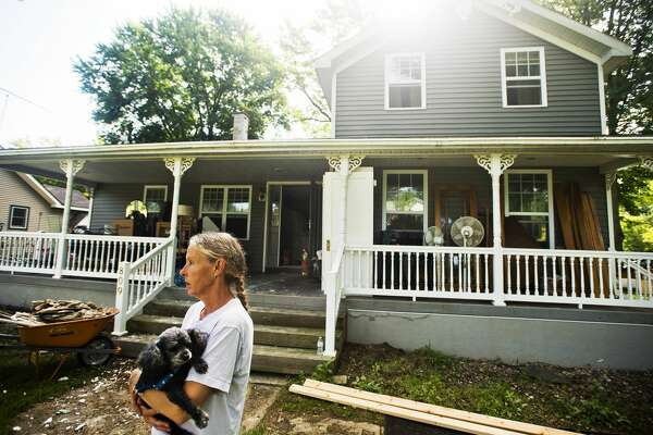 Peggy Sue Ginter stands in her front yard with her dog, Jesse, as a group from Team Rubicon works to gut the inside of her home, which was severely damaged by recent flooding, on Tuesday, July 11, 2017 on Atwell Street near Poseyville Road.