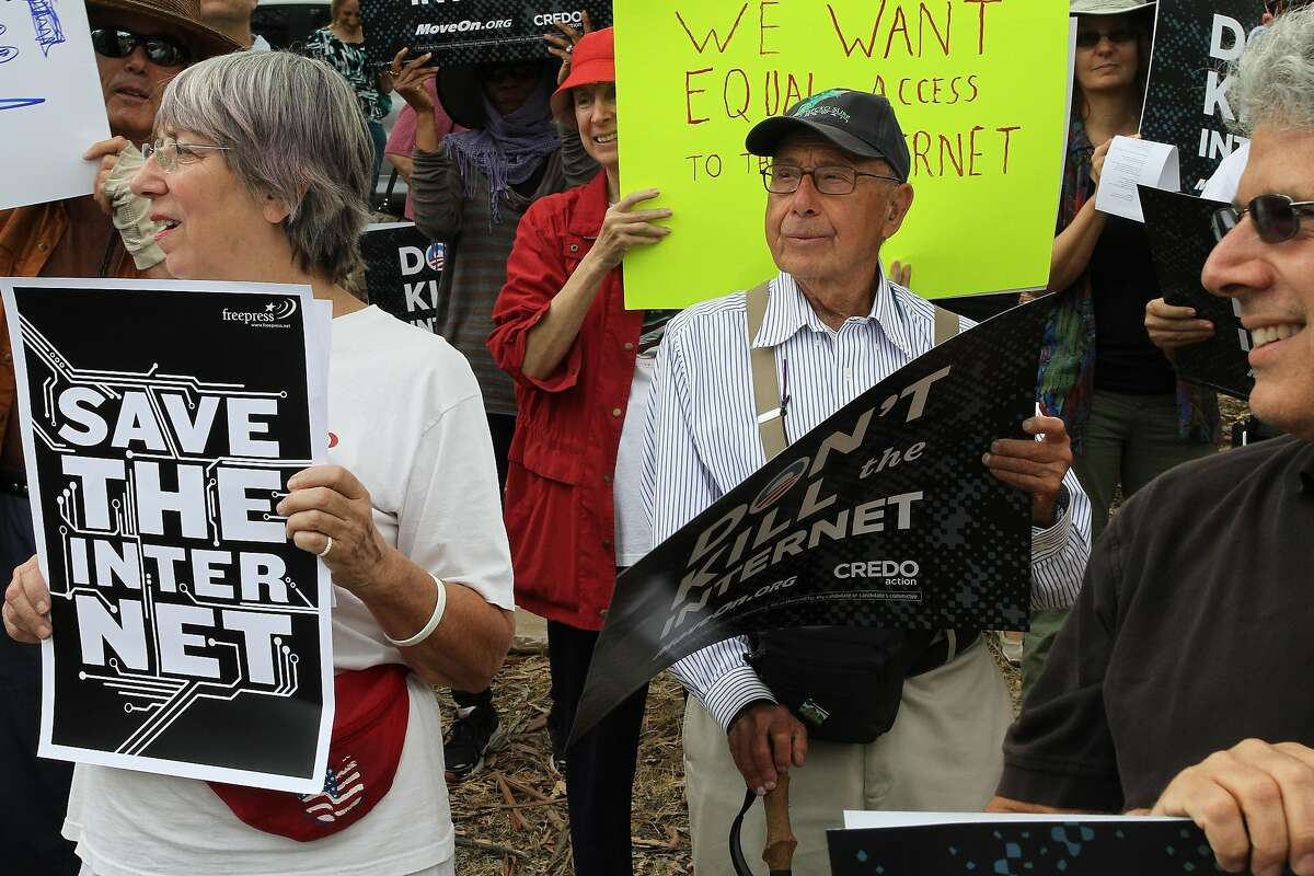Larry Aronson, center, looks on as protesters chant about net neutrality on Page Mill Rd. on Wednesday, July 23, 2014 in Los Altos, Calif. Protesters interested in net neutrality and conflicts abroad gathered at the corner of Page Mill Rd. and Arastadero to express their concerns.