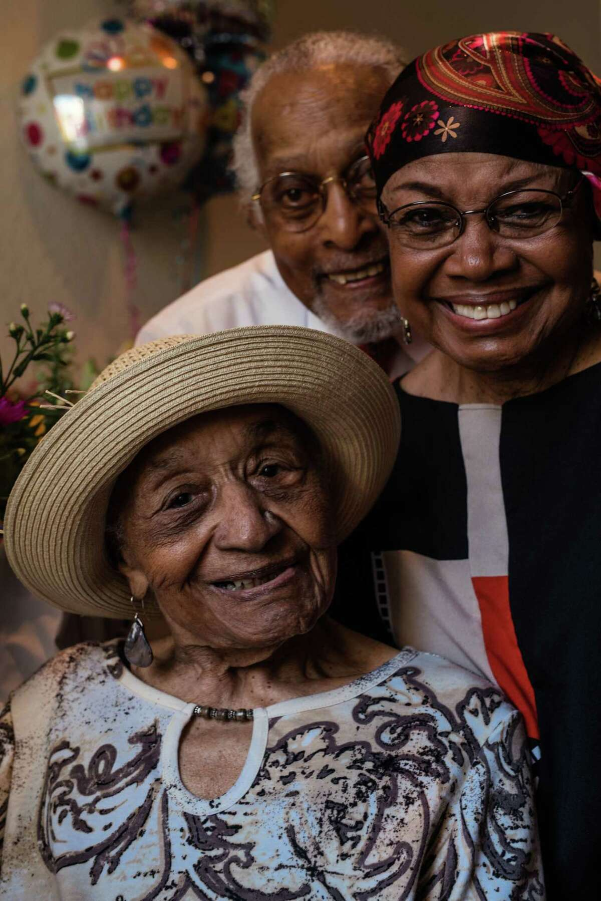 103-year-old Georgia Mitchell poses for a photo with her daughter, Bernice Satterwhite, and son in law, at her birthday party July 8, in the house that flooded during hurricane Harvey.