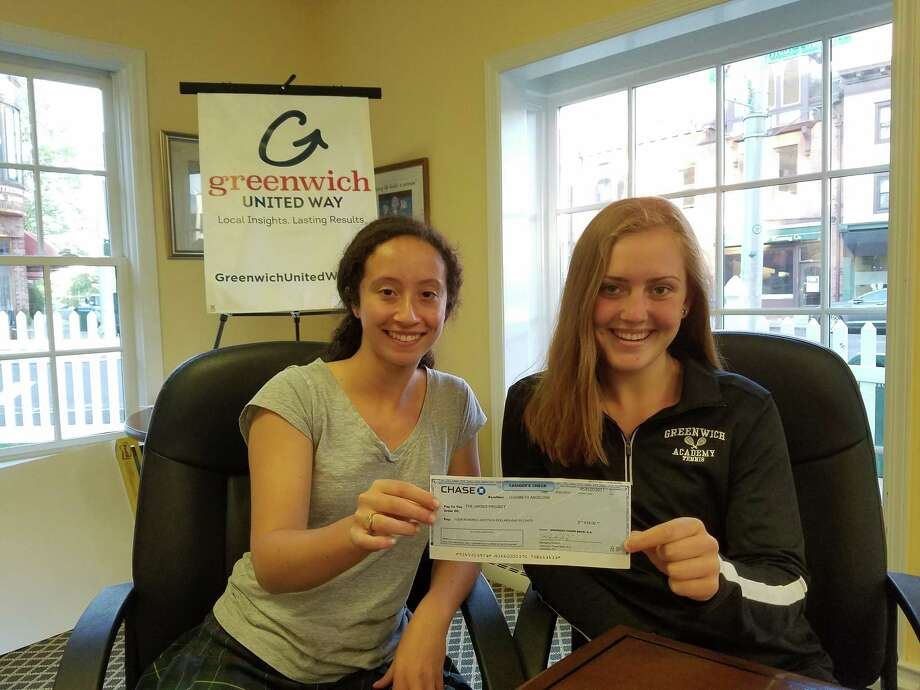 Zoe Morris and Kate Miele hold a $1,000 check for the Undies Project, raised through teens volunteering with Greenwich Junior United Way. Photo: Contributed Photo / Greenwich Junior United Way
