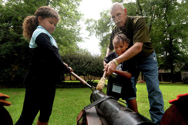 From left, Laila Brown, 7, and Janiyah Living, 7, take position under the guidance of Ron Schroeder as they and members of their group learn the steps to firing a canon, as would soldiers of the 1800's. The hands-on activity is among many planned for children in the Beaumont Heritage Society's annual Camp Lookinback, which began Tuesday. Held on the grounds of the John Jay French Museum, it offers a fun, educational look at the life and style of the 1800's, ranging from canon firing to crafts, and the work of war time lady spies to cooking. Photo taken Tuesday, July, 11, 2017 Kim Brent/The Enterprise