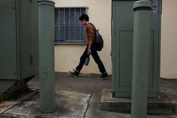 Local resident Brian Dentino walks past AT&T utility boxes in the Outer Sunset July 11, 2017 in San Francisco, Calif.