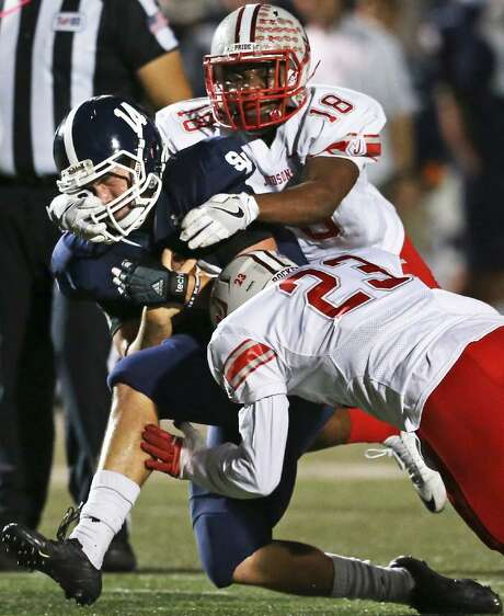 Minimizing brain trauma is the motivation behind new helmet technology. Hits to the head are an issue at all levels of football, including high school, where Smithson Valley quarterback Josh Adkins is tackled by Judson's Jovan Holmes and Harold Watson on Oct. 28, 2016. Photo: Express-News Photo /