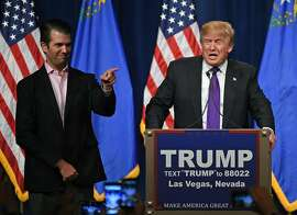 """LAS VEGAS, NV - FEBRUARY 23:  Donald Trump Jr. (L) looks on as his father, Republican presidential candidate Donald Trump, waves after speaking at a caucus night watch party at the Treasure Island Hotel & Casino on February 23, 2016 in Las Vegas, Nevada. The New York businessman won his third state victory in a row in the """"first in the West"""" caucuses.  (Photo by Ethan Miller/Getty Images)"""