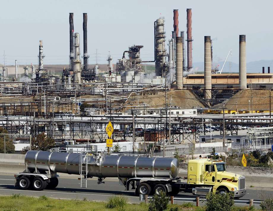 A tanker truck passes the Chevron refinery in Richmond. Chevron is one of the defendants in lawsuits filed Monday by Marin and San Mateo counties and Imperial Beach in San Diego County, seeking to hold energy companies liable for the effects of climate change. Photo: Paul Sakuma, Associated Press