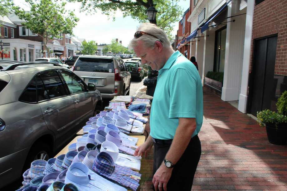 John Frieders, of New Canaan, looks through piles of shirts at the New Canaan Sidewalk Sale July 15, 2016. Photo: Justin Papp / Hearst Connecticut Media / New Canaan News