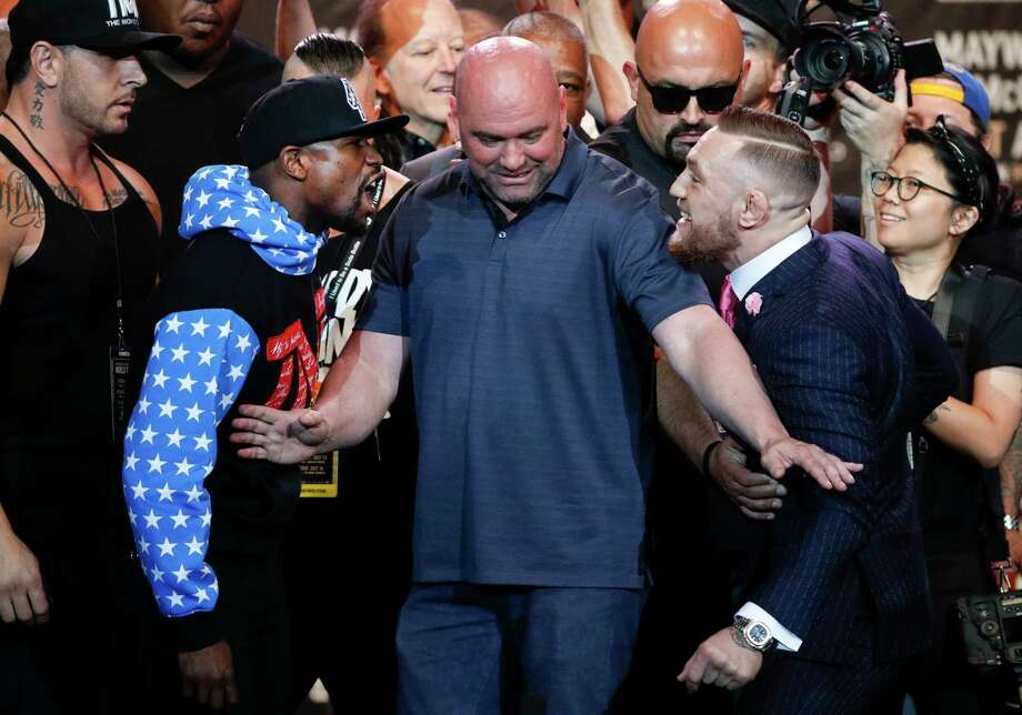 UFC president Dana White, center, intervenes as boxer Floyd Mayweather Jr., left, and mixed martial arts fighter Conor McGregor exchange words during a news conference at Staples Center Tuesday, July 11, 2017, in Los Angeles. The two are scheduled to fight in a boxing match in Las Vegas on Aug. 26. (AP Photo/Jae C. Hong) Photo: Jae C. Hong, Associated Press / Copyright 2017 The Associated Press. All rights reserved.