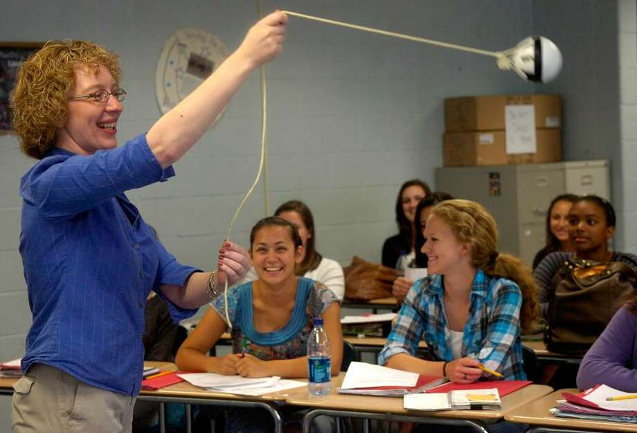 Kristen Record swings a ball over her head as she teaches Honors Physics at Bunnell High School Thursday, June 10, 2010. The demonstration was part of Record's explaination of the Doppler Effect and the way distance and motion effect pitch. Photo: Lindsay Niegelberg / Connecticut Post