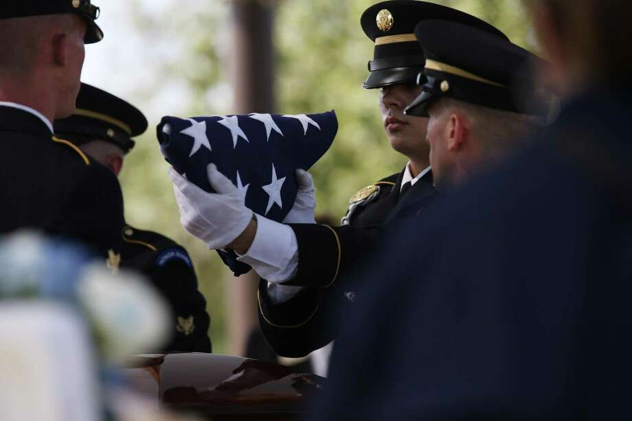 The honor guard prepares the U.S. flag for presentation to family members during burial services for U.S. Army Cpl. Frank Luna Sandoval at Fort Sam Houston National Cemetery, Tuesday, July 11, 2017. Sandoval was missing action and presumed dead since the Korean War. Sandoval was 20-years-old when he was take as a prisoner of war and died of malnutrition. Sandoval was reported missing in action on Feb. 13, 1951 and declared dead over two and a half years later. He body was returned to U.S. custody in 1954 and he was buried as an unknown soldier in Hawaii for decades. The family was notified of his identification early this year. Photo: JERRY LARA / San Antonio Express-News / San Antonio Express-News