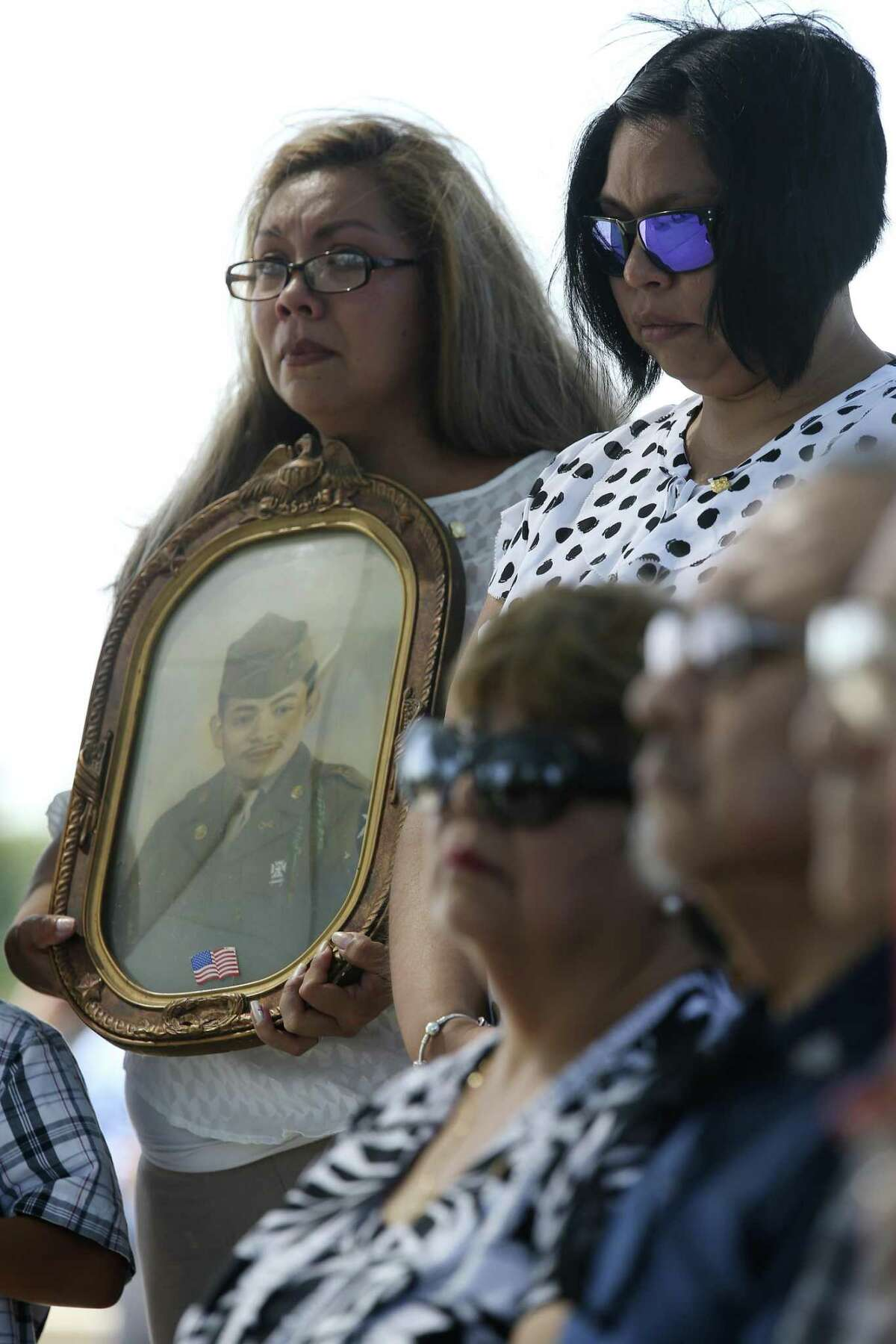 Melanie Sandoval Dacosta holds a portrait of her grandfather, U.S. Army Cpl. Frank Luna Sandoval, during his burial ceremony at Fort Sam Houston National Cemetery, Tuesday, July 11, 2017. Sandoval was missing action and presumed dead since the Korean War. Sandoval was 20-years-old when he was take as a prisoner of war and died of malnutrition. Sandoval was reported missing in action on Feb. 13, 1951 and declared dead over two and a half years later. He body was returned to U.S. custody in 1954 and he was buried as an unknown soldier in Hawaii for decades. The family was notified of his identification early this year.