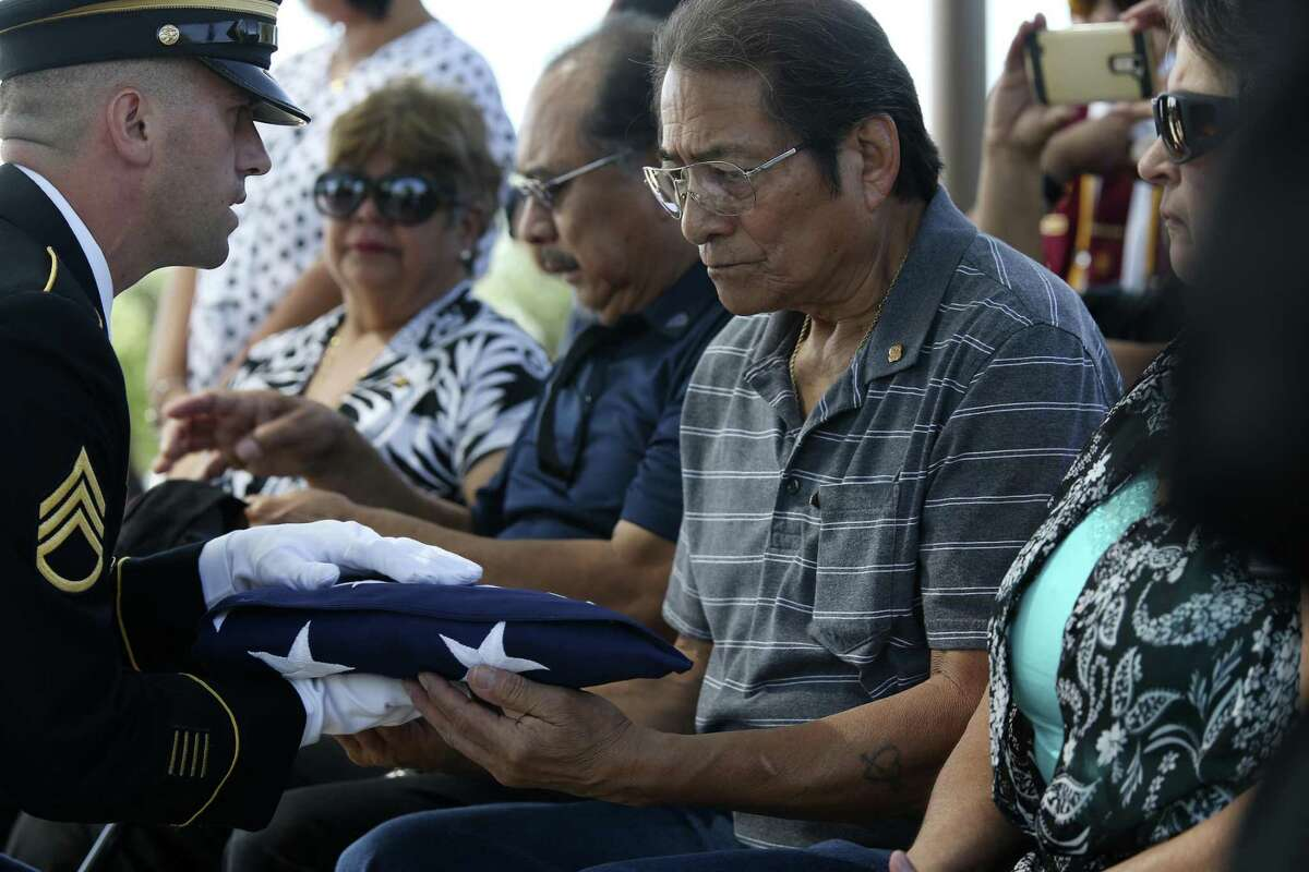Alex Sandoval, 69, is presented with a flag during the burial ceremony for his father, U.S. Army Cpl. Frank Luna Sandoval, at Fort Sam Houston National Cemetery, Tuesday, July 11, 2017. Sandoval was missing action and presumed dead since the Korean War. Sandoval was 20-years-old when he was take as a prisoner of war and died of malnutrition. Sandoval was reported missing in action on Feb. 13, 1951 and declared dead over two and a half years later. He body was returned to U.S. custody in 1954 and he was buried as an unknown soldier in Hawaii for decades.