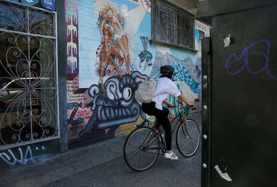 A cyclist rides past a utility box in front of Belmar La Gallinita Meat Market on 24th Street in the Latino Cultural District. Photo: Leah Millis / The Chronicle