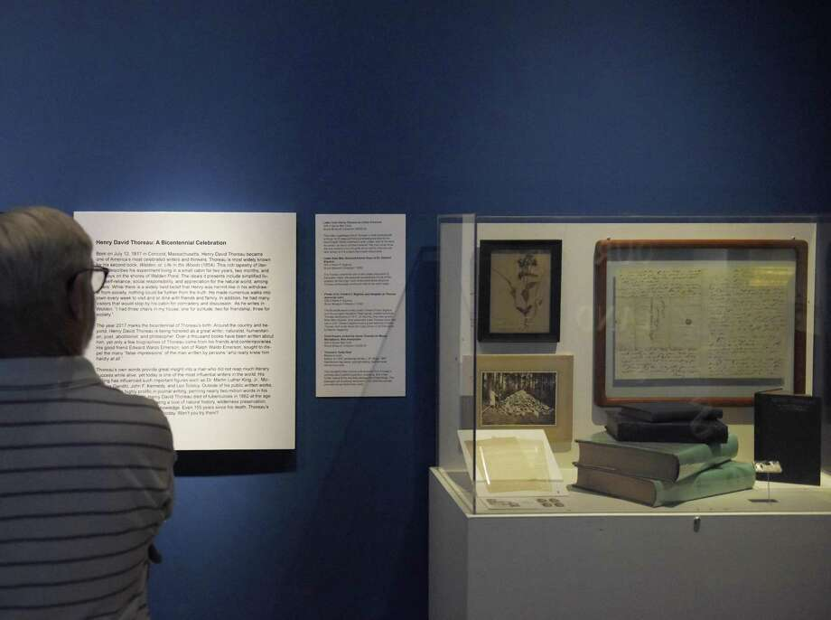 "New Haven's Michael Shanahan looks at items displayed at the ""Henry David Thoreau: A Bicentennial Celebration"" exhibition at the Bruce Museum in Greenwich, Conn. Tuesday, July 11, 2017. Books, letters and a bouquet of flowers comprise the small display commemorating the bicentennial of the ""Walden"" author's birth, July 12, 1817. The display will remain at the Bruce Museum through the end of July. Photo: Tyler Sizemore / Hearst Connecticut Media / Greenwich Time"