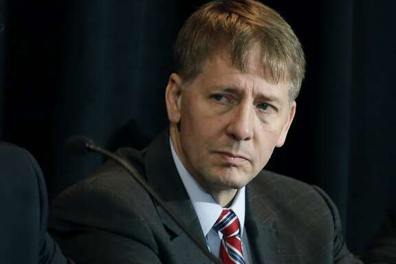 FILE - In this Oct. 7, 2015, file photo, Consumer Financial Protection Bureau Director Richard Cordray listens to a speaker during a hearing in Denver. The CFPB has decided to broadly ban the use of so-called arbitration clauses from financial products. Cordray said mandatory arbitration clauses are a way for banks and other financial companies to �sidestep the legal system.� Consumer advocates have been pushing for years for stricter federal regulation of these types of clauses. But the move is likely to face pushback from the banking industry and the Republican-controlled Congress. (AP Photo/Brennan Linsley, File)