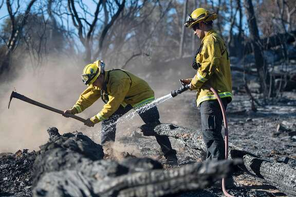 Bryce Briare (R) and Mike Manibusan (L) with the Marin County Fire Deptartment work on a smoldering hotspot as firefighters continue to build towards containment of the Wall fire in Oroville, California on July 10, 2017.  More than a dozen wildfires were raging across California July 10, 2017, forcing thousands of residents of the most populous US state to flee their homes. / AFP PHOTO / JOSH EDELSONJOSH EDELSON/AFP/Getty Images