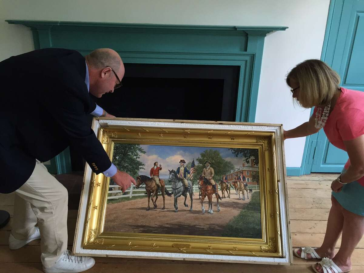 David Hayes, left, with Schuyler Mansion historic site manager Heidi Hill look over a painting of Hamilton, George Washington and Philip Schuyler on horseback after a 1783 meeting in Albany that Hayes commissioned from noted painter Len Tantillo. Hayes has loaned the painting to the Schuyler Mansion for this weekend's 100th anniversary celebration of the house as a state-run historic site. (Paul Grondahl /Times Union)