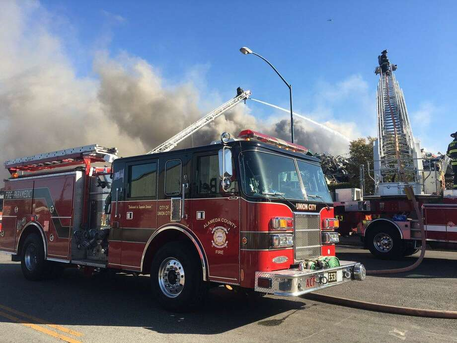A fire burning at a salvage yard in San Leandro sent smoke swirling for miles on Tuesday night. Photo: Alameda County Fire Department / Alameda County Fire Department