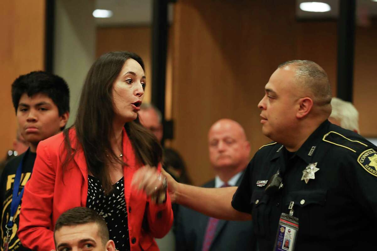 Lauren Summerville, a member of Pantsuit Republic Houston, is ejected from the Harris County Commissioners Court after protesting against the commissioners decision not to join the lawsuit against the state's sanctuary cities law.